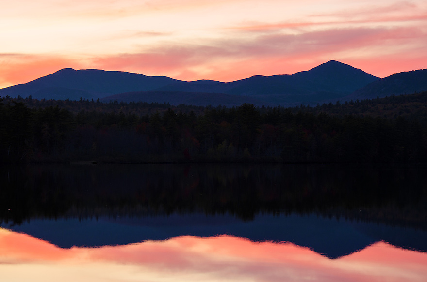 Sunsets warm glow is reflected in Chocrua Lake in front of Mts. Whiteface and Passaconaway.