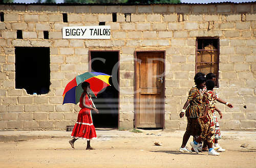 """Victoria Falls, Zambia. """"Biggy Tailors"""", girl in red dress with multicoloured umberella."""
