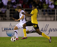 Andrew Oliver (16) of the United States is fouled by Alvas Powell (5) of Jamaica during the semifinals of the CONCACAF Men's Under 17 Championship at Catherine Hall Stadium in Montego Bay, Jamaica. The United States defeated Jamaica, 2-0.