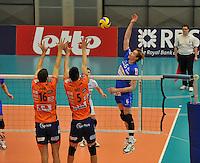 Knack Roeselare - ACH Volley Ljubljana : Sam Deroo met de smash over het blok van Matej Vidic (links) en Alen Sket (midden).foto VDB / BART VANDENBROUCKE
