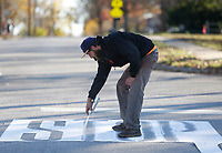 Sam Blevins, with Action Asphalt Sealcoating and Striping, traces Tuesday, November 17, 2020, a traffic control stencil of the word stop at the intersection of W. Cypress Street and S. 7th Street in Rogers. The stencil was applied to all ways and was then covered in thermo melted plastic. Check out nwaonline.com/201118Daily/ and nwadg.com/photos for a photo gallery.(NWA Democrat-Gazette/David Gottschalk)