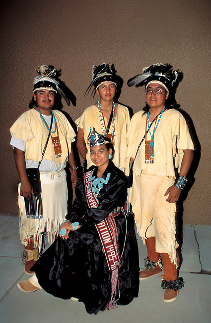 Miss Navajo dressed in traditional velvet dress complimented by turquoise jewelery poses with the Pollen Trail Dancers dressed in traditional historic deerskin clothing and feather headdresses of the Navajo