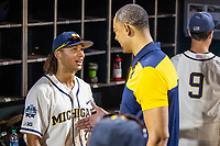 Michigan Wolverines outfielder Jordan Brewer (22) talks with Men's Basketball coach Juwon Howard after beating the Vanderbilt Commodores in Game 1 of the NCAA College World Series Finals on June 24, 2019 at TD Ameritrade Park in Omaha, Nebraska. Michigan defeated Vanderbilt 7-4. (Andrew Woolley/Four Seam Images)