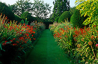 In a sheltered part of the garden a long manicured lawn is lined with beds planted with a variety of flowering perennials and shrubs