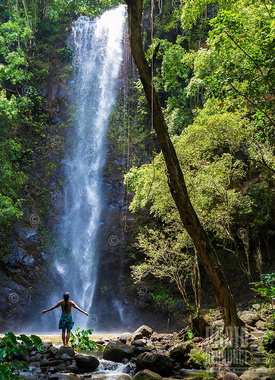 A woman soaks in the sun and water at Uluwehi Falls, Kaua'i.