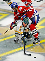 3 February 2008: University of Vermont Catamounts' forward Dean Strong, a Junior from Mississauga, Ontario, reaches for the puck as he is checked by University of Massachusetts Lowell River Hawks' forward Ben Holmstrom, a Sophomore from Colorado Springs, CO, at Gutterson Fieldhouse in Burlington, Vermont. The Catamounts defeated the River Hawks 3-2...Mandatory Photo Credit: Ed Wolfstein Photo