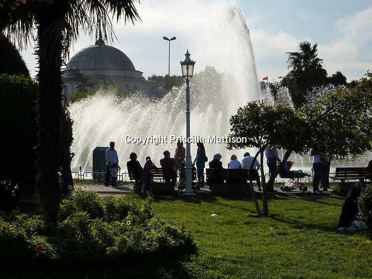 Istanbul, Turkey - September 24, 2009:  People are silhouetted in front of a fountain in Sultan Ahmed Square.
