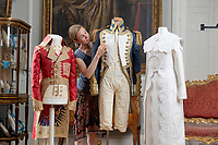 BNPS.co.uk (01202) 558833<br /> Pic: ZacharyCulpin/BNPS<br /> <br /> Pictured: Artist Stephanie Smart with the incredible paper outfits. (From left) a coat inspired by Napoleon, an early 19th century British naval uniform, and a stunning Regency 'walking dress'.<br /> <br /> A textile artist has unveiled a collection of remarkable Regency outfits she has painstakingly made out of paper.<br /> <br /> Stephanie Smart has produced 11 life-sized outfits including a red frockcoat modelled on the style of Napoleon.<br /> <br /> Others depict walking dresses, naval uniforms and spencer jackets from the Regency era. (1795-1837)<br /> <br /> Her creations are on display as part of an exhibition titled The Regency Wardrobe at Firlie Place in East Sussex.