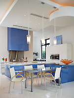The gloss modern blue & white kitchen is a clean backdrop for art collections and entertaining