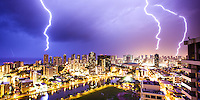 A 30-second exposure shows three buildings across O'ahu's Waikiki and Honolulu being simultaneously struck by lightning on March 5, 2012; the bolt hitting the Hilton Hawaiian Village is reflected in the Ala Wai Canal, and a fourth bolt hits the sea on the left.