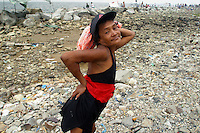 "Aling Remy, aka ""Kokwang"", strikes a pose for the camera while taking a break from bathing at a rocky stretch of shore by the GSIS compound in Pasay City. She along with hundreds other Metro Manila residents who cannot afford a trip to the provinces made do with the modest and sometimes trashy beaches of Manila Bay on Black Saturday. 26 march 2005"