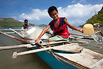 Two young Filipino boys work on their family's wooden bangka boat in the tiny fishing village of Vigan near Snake Island and El Nido, in the Bacuit Archipelago in Palawan, Philippines.