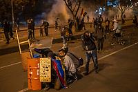 BOGOTA - COLOMBIA, 25-05-2021: Manifestantes de la primera línea se resguardan del ataque con gases lacrimógenos y aturdidoras por parte del ESMAD (Escuadrón Móvil Antidisturbios de la Policía) durante los disturbios en el sector de las Américas de la ciudad de Bogotá durante el día 28 del Paro Nacional en Colombia hoy, 25 de mayo de 2021, para protestar contra el gobierno de Ivan Duque además de la precaria situación social y económica que vive Colombia. El paro fue convocado por sindicatos, organizaciones sociales, estudiantes y la oposición. / Demonstrators from the front line protect themselves from the attack with tear gas and stun guns by the ESMAD (Police Anti-Riot Mobile Squad) during the riots at Portal Las Americas sector of the city of Bogota during the day 28 of the National strike in Colombia today, May 25, 2021, to protest against the government of Ivan Duque in addition to the precarious social and economic situation that Colombia is experiencing. The strike was called by unions, social organizations, students and the opposition in Colombia. Photo: VizzorImage / Diego Cuevas / Cont