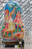 Moscow, Russia, 15/06/2011..A security guard is dwarfed by an enormous painted wooden doll at an exhibition of giant Russian matryoshki, or nesting dolls, in the newly-opened Afimall shopping centre. The dolls, designed by Boris Krasnov, are from 6 to 13 metres high, and each is decorated in a different style of traditional Russian folk art.