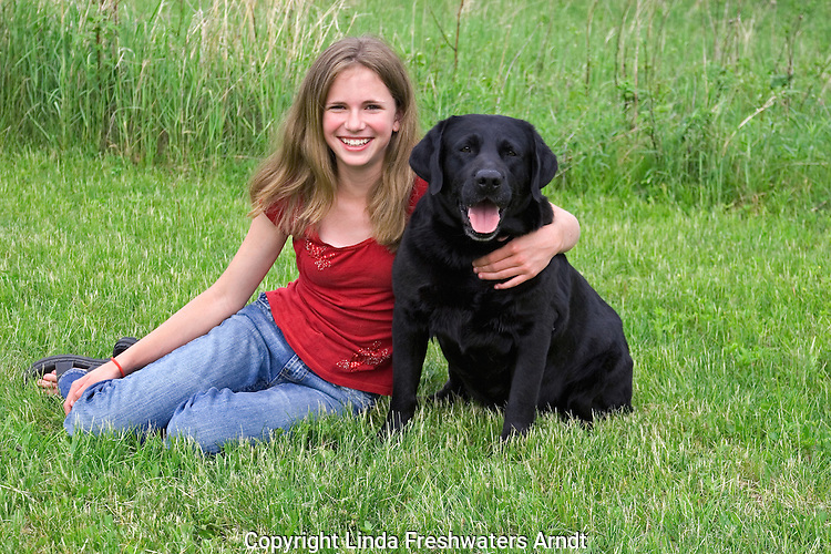 Black Labrador retriever (AKC) posing with a 13 year old girl.  Summer. Winter, WI.