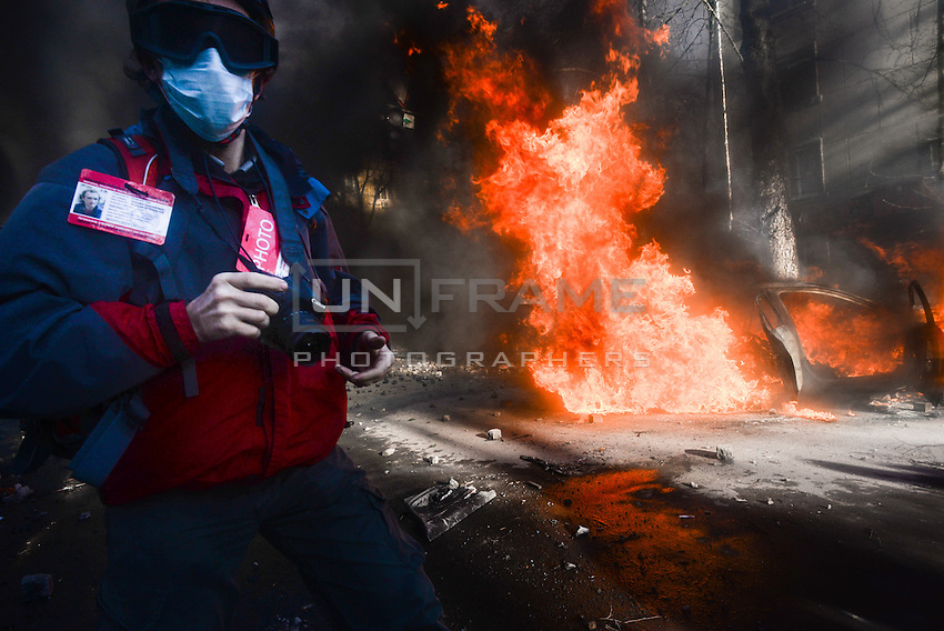 Press-photographer reporting from the barricades during protests. Kiev, Ukraine. Feb. 18, 2014. (Photo by Msyslav Chernov / UnFrame)