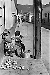 San Cristobal de las Casas, Mexico. Indigenous Indian girl child and sibling selling apples in the street. The material on the girld head acts as shade while selling stuff and padding when she head carries the basket of produce she is selling. 1973