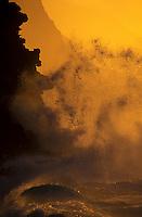 Waves crashing against the cliffs at Ke e, Kauai during sunset