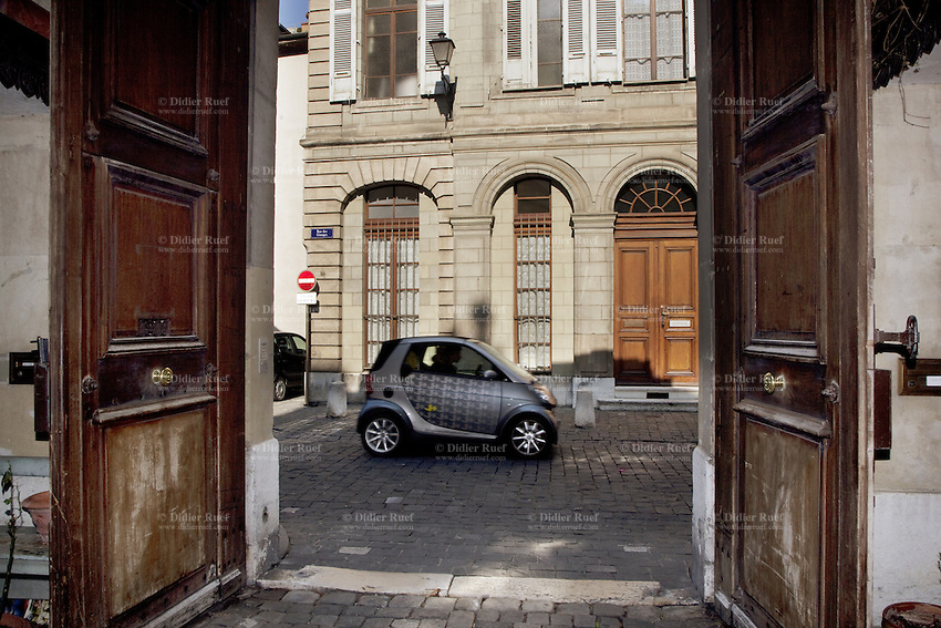 """Switzerland. Geneva. The """" rue des Granges """" is a narrow street in the old city. View from the courtyard of a private mansion on the street where passes a grey Smart car.  12.03.2010 © 2010 Didier Ruef"""