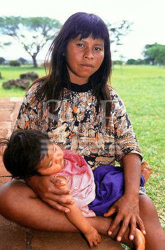 Rio Grande do Sul, Brazil. Guarani Indian mother with sleeping daughter in her lap, looking into the camera.