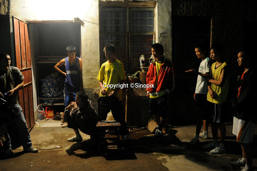 Young boxers outside their dorm with trainer,  near Huili Middle School in Sichuan Province, China. The group of young boxers are hoping to make it to become some of China's first professional boxers...PHOTO BY SINOPIX