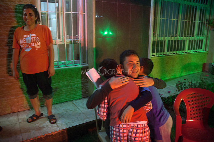 31/10/14. Erbil, Iraq. At the end of the farewell party Wassam (left) and Milad (right), hug Willaim, a family friend, as they say goodbye to him.