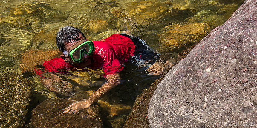 Fine Art Photograph of a local Mexican searching with his hands under the rocks for shrimps and clams in the Rio Cuale river, in Puerto Vallarta, Mexico.