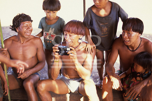 Pavuru Village, Brazil. Village man with red urucum dyed hair inspecting a camera.