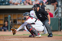 Billings Mustangs catcher Pabel Manzanero (64) sets a low target as home plate umpire Phil Bando looks on during the game against the Missoula Osprey at Dehler Park on August 21, 2017 in Billings, Montana.  The Osprey defeated the Mustangs 10-4.  (Brian Westerholt/Four Seam Images)