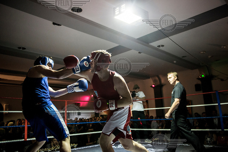Danny Williams (right) fights Lee Klinger at a white collar boxing event at the London Irish Centre where the 'Carpe Diem' boxing event is taking place. <br /> <br /> 'White-collar boxing' is a growing phenomenon amongst well paid office workers and professionals and has seen particular growth in financial centres like London, Hong Kong and Shanghai. It started at a blue-collar gym in Brooklyn in 1988 with a bout between an attorney and an academic and has since spread all over the world. The sport is not regulated by any professional body in the United Kingdom and is therefore potentially dangerous, as was proven by the death of a 32-year-old white-collar boxer at an event in Nottingham in June 2014. The London Irish Centre, amongst other venues, hosts a regular bout called 'Carpe Diem'. At most bouts participants fight to win. Once boxers have completed a few bouts they can participate in 'title fights' where they compete for a replica 'belt'.