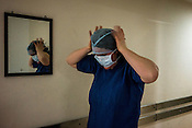 Der Spiegel journalist, Vivian Pasquet wears the protective gear before going to the operation theatre at the St. Stephen's Hospital in Delhi, India.