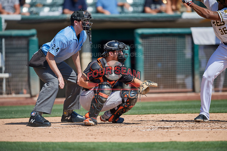 Jamie Ritchie (16) of the Fresno Grizzlies on defense as umpire Nate Tomlinson handles the calls behind the plate during a game against the Salt Lake Bees at Smith's Ballpark on September 3, 2018 in Salt Lake City, Utah. The Grizzlies defeated the Bees 7-6. (Stephen Smith/Four Seam Images)
