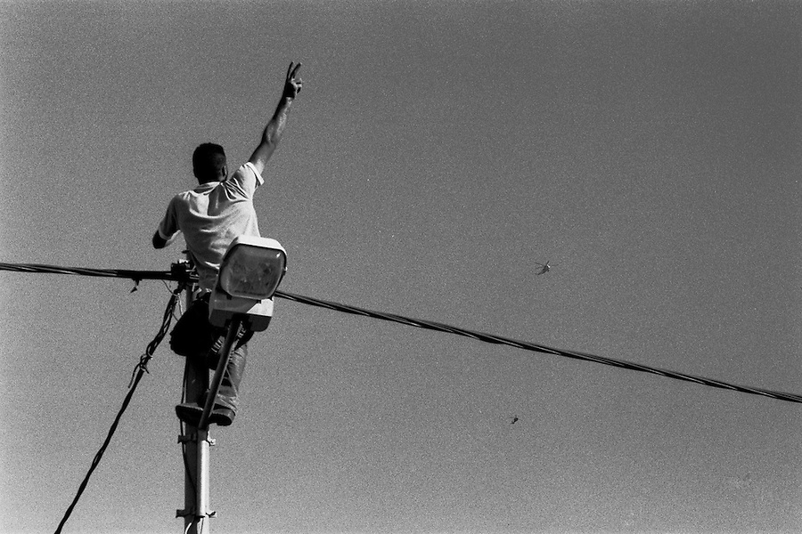 Yound man on top of light post welcomes the two helicopters bringing Yasser Arafat's body from Egypt to the Muqata presidential compound the day of the funeral.