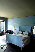 The wooden bed in the master bedroom has been painted the same soft blue as the walls, with the addition of a 1950s armchair upholstered in royal blue velvet