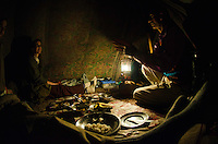 Interior view of Kashmiri trekking tent with travelers eating a meal with guide, Kanka River, near Naranag, Kashmir, India.