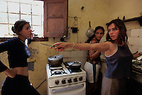 Ariadna Del Carmen Rodriguez points a knife at her roommate in their kitchen. She is a single girl in the Cuban Underground. Ariadna is a young woman trying to lead an independent life and follow her dreams. Working as an actress in the theater, her charm is a mixture of innocence and a theatrical personality. She lives with a roommate in the city of Havana while she is going to school. She and her room mate are both actresses and wander through the academic and Cuban underground of artists and friends