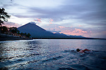 A swimmier swims towards Gunung Agung in the western part of Bali, Indonesia