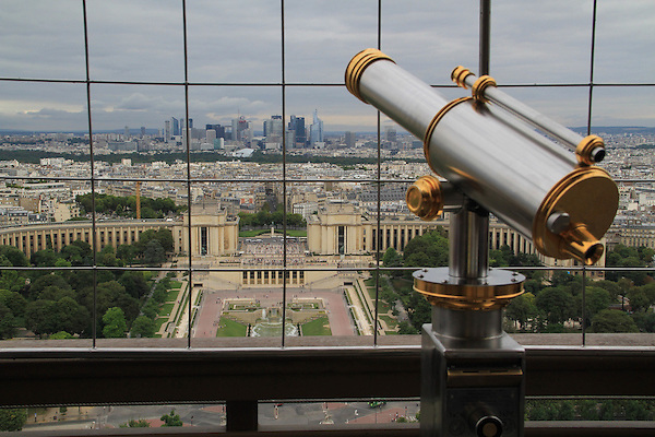 France, Paris.  <br /> Step back and make a composition that invites the viewer into the image, so they can imagine being there. Telescopes are personal icons, I make it a point to add them to my images because they often work. The wire fencing helps diminish a cloudy sky. <br /> Telescope and downtown Paris from Eiffel Tower.
