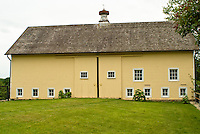 Pretty yellow painted barn with white windows, sliding doors, sky, green grass. Agricultural farming building