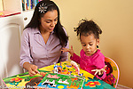 Two year old toddler girl language development talking with mother mother as they play with animal puzzle pieces