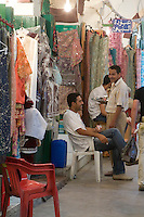 Tripoli, Libya. Medina, Clothing and Fabric Suq, Waiter Serving Coffee.