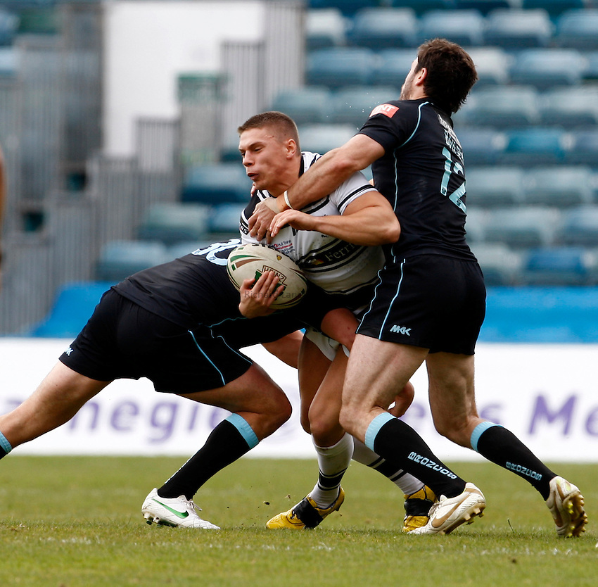 Photo: Richard Lane/Richard Lane Photography. London Broncos v Hull FC. Stobart Super League. 20/05/2012. Hull's Matthew Russell is tackled by Broncos' Mark Bryant and Chris Bailey.
