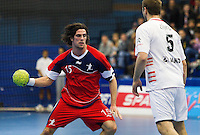 08 JAN 2012 - LONDON, GBR - Great Britain left back Martin Hare (#15, in red) looks for a way past Austria's Vytautis Ziura (#5, in white)  during the men's 2013 World Handball Championships qualification match at the National Sports Centre in Crystal Palace, Great Britain (PHOTO (C) 2012 NIGEL FARROW)