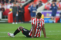 Ethan Pinnock of Brentford awaits treatment on the pitch after suffering an injury during Brentford vs Liverpool, Premier League Football at the Brentford Community Stadium on 25th September 2021