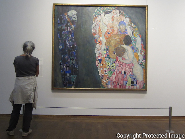 """Gustav Klimt, Death and Life<br /> <br /> Gustav Klimt's large painting Death and Life, created in 1910, features not a personal death but rather merely an allegorical Grim Reaper who gazes at """"life"""" with a malicious grin. This """"life"""" is comprised of all generations: every age group is represented, from the baby to the grandmother, in this depiction of the never-ending circle of life. Death may be able to swipe individuals from life, but life itself, humanity as a whole, will always elude his grasp. The circle of life likewise repeats itself in the diverse, wonderful, pastel-coloured circular ornaments which adorn life like a garland. Gustav Klimt described this painting, which was honoured with a first prize at the 1911 International Art Exhibition in Rome, as his most important figurative work. Even so, he seems to suddenly no longer have been satisfied with this version in 1915, for he then began making changes to the painting—which had been framed for long by that time. The background, reportedly once gold-coloured, was made grey, and both death and life were given further ornaments. Standing before the original and examining the left interior edge of Josef Hoffmann's frame for the painting, one can still discern traces of the subsequent over-painting, which was done by Klimt himself."""