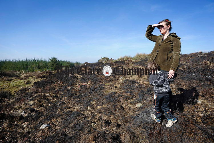 Locals Sarah and Jules Mortimer survey the damage caused by gorse fires in the Ballinruan area on St Patrick's night. Photograph by John Kelly.