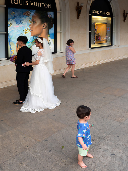 The bride and Groom outside the Louis Vuitton shop waiting for the Photographer while a child crashes the party. Everyday life in the streets of Hanoi, Vietnam