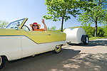 A woman is waiving from her two-toned yellow and white 1958 Nash Metropolitan. Hitched to the car is a white teardrop vintage travel trailer.