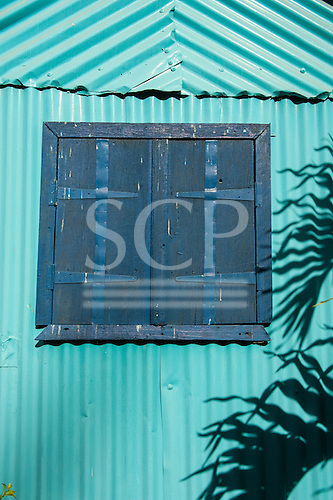 Flic en Flac, Mauritius. Closed blue shutters on a tourquoise corrugated wall with palm leaf shadow.