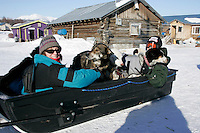 Monday March 12, 2007   ----   Kaltag checker Sally Hamm and veterinarian Tracy Garza sit in a sled with a load of dropped dogs waiting to be towed to the airport and be flown out.